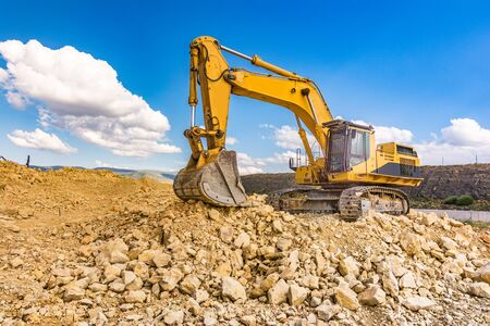 Photo pour Excavator in a quarry extracting stone and rock - image libre de droit