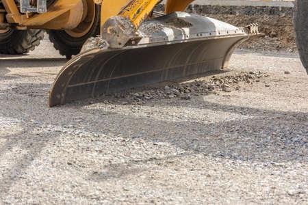 Foto de Paving the ground at road construction works with a bulldozer - Imagen libre de derechos