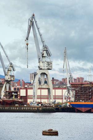 Foto de Cranes in the shipyard over cloudy sky - Imagen libre de derechos