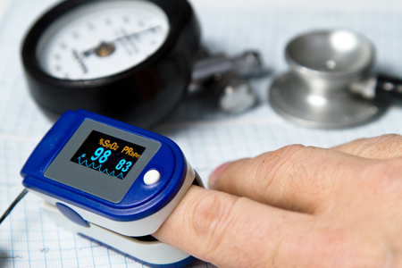 Foto de A pulse oximeter used to measure pulse rate and oxygen levels with Sphygmomanometer and medical stethoscope and ECG background - Imagen libre de derechos