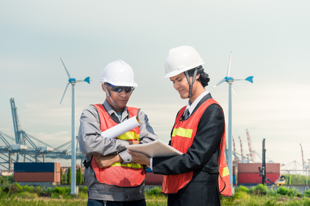 Photo pour Male and businessman Industrial Engineers Look at Project Blueprints While Standing Surround by Pipeline Parts in the Enormous Heavy Industry Manufacturing Factory,container,transport,electric turbine,port - image libre de droit