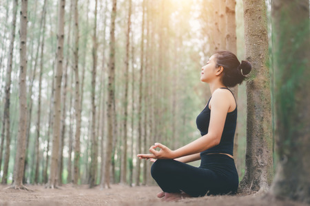 Foto per Young female relaxes in yoga pose in green nature - Immagine Royalty Free
