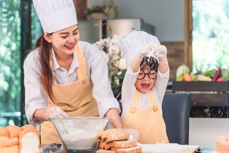 Foto per Young family cooking food in kitchen. Happy young girl with her mother mixing batter in the bowl. - Immagine Royalty Free