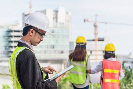 Photo pour Business, building, industry, technology and people concept - smiling builder in hardhat with tablet pc computer over group of builders at construction site - image libre de droit