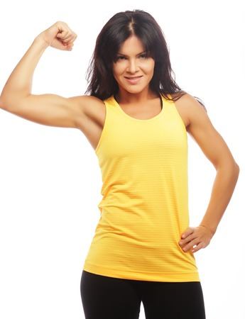 Cheerfully smiling  sporty woman demonstrating biceps, isolated on white backgroundの写真素材