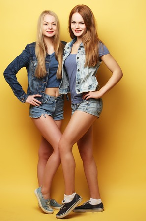 Full body portrait of two  hipster girls over yellow background