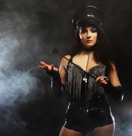 Sexy brunette woman mistress holding whip,over dark backgrouynd with smoke