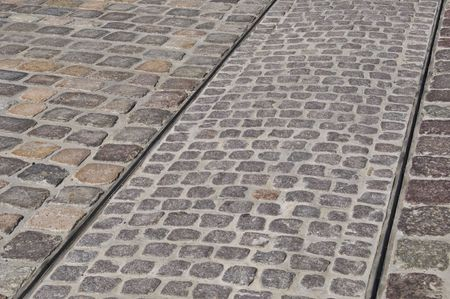 tracks of a tram on a cobblestone pavement