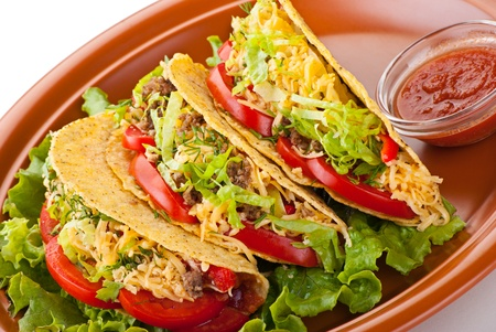 Closeup of beef tacos served with salad and fresh tomatoes salsa on white background