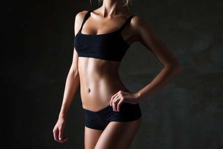 Photo pour Slim tanned woman\'s body  over dark gray background - image libre de droit