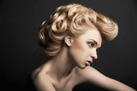 Foto de Beautiful high fashion female model with abstract hair style behind the table - Imagen libre de derechos