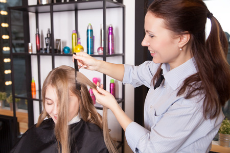 Portrait of stylist making curls hair in salon