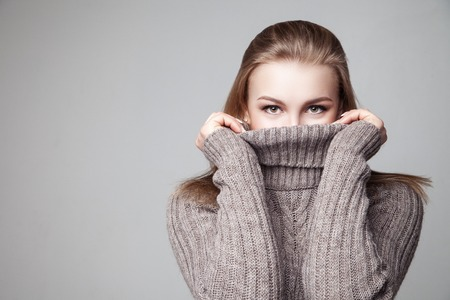 Beautiful blond young girl wears winter pullover over gray background
