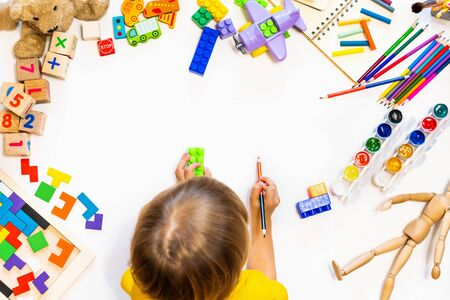 Photo for Prescool boy drawing on floor on paper. Kid play with blocks, plane and cars. Educational toys for preschool and kindergarten child, Child at home or daycare. Top view - Royalty Free Image