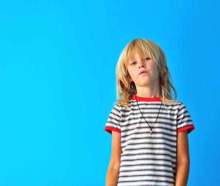 Foto de Portrait of a cute blonde boy at blue wall background - Imagen libre de derechos