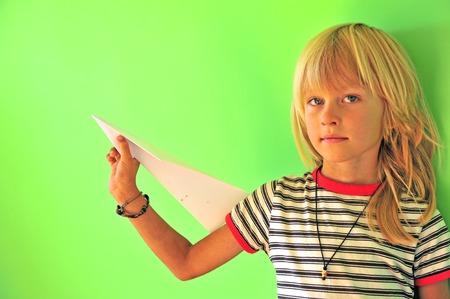 Foto de Little boy with paper airplane at green wall background - Imagen libre de derechos