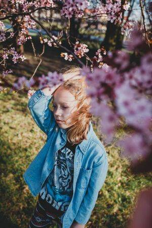 cute sad girl with disheveled hair on a Sunny day. natural beauty, a delicate girl\'s face, naturalness, a teenager, a daughter stands on the street in the spring. European child in a blooming Park, the concept of a happy childhood and the aroma of cherrie