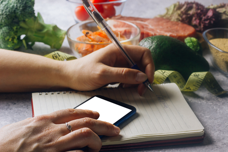 Photo for Woman using calorie counter application on her smartphone - Royalty Free Image