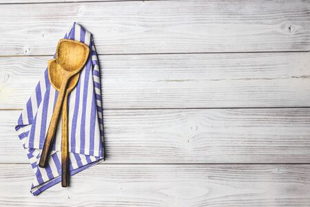 Photo for Cooking wooden utensils, olive oil, spices and light blue, white napkin on white wooden - Royalty Free Image