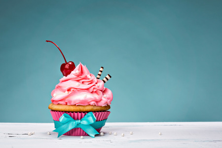 Cupcake with pink buttercream icing and a cherry on top.