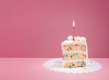 Photo for Slice of Colorful Birthday Confetti Cake with a lit candle over a pink background. - Royalty Free Image