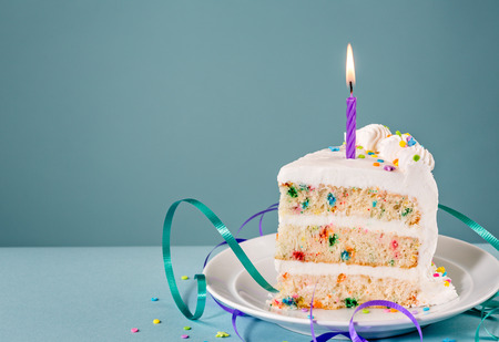 Photo for Slice of Birthday Cake with a lit candle and ribbons over a blue background. - Royalty Free Image