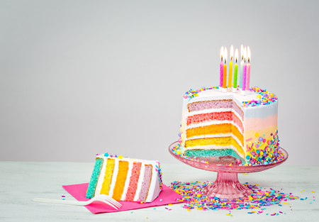 Photo pour Colorful rainbow layered Birthday cake with lit candles and sprinkles - image libre de droit