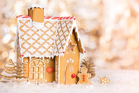Photo pour Homemade gingerbread house scene on warm bokeh background - image libre de droit