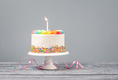 Photo pour White Birthday cake with rainbow icing, colorful Sprinkles and one candle over a gray - image libre de droit