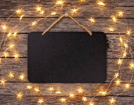 Photo pour Blank chalkboard sign with string lights hanging from wooden background. - image libre de droit