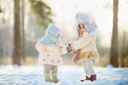 Winter portrait of little girl in fur coat at sunny park
