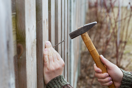 man hands drive nail with a hammer in wooden fence, carpentry