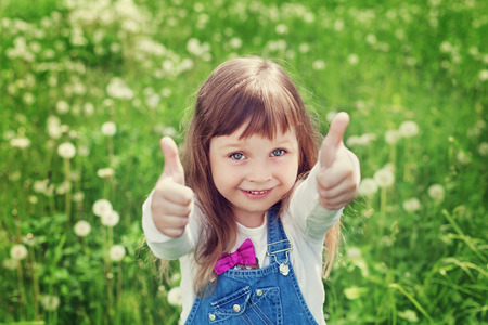 portrait of cute little girl with thumbs up shows a class on the flower meadow, happy childhood concept, child having fun, vintage toned