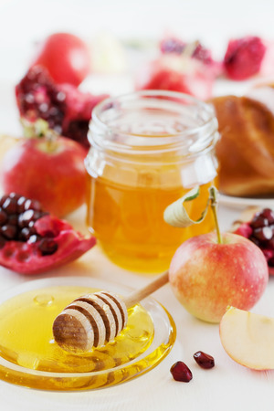 Honey, apple, pomegranate and hala, table set with traditional food for Jewish New Year Holiday, Rosh Hashanaの写真素材