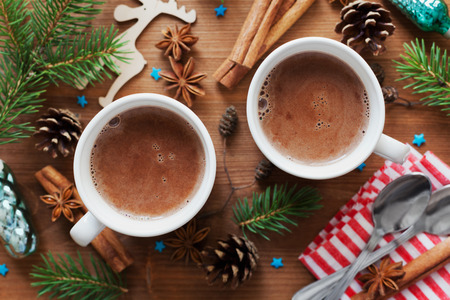 Two cups of fresh hot cocoa or hot chocolate on wooden christmas background, top view