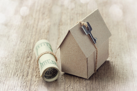 Model of cardboard house with key and dollar bills  House