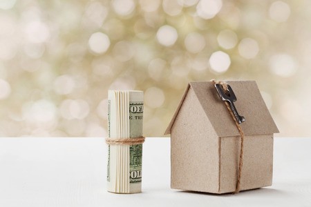 Model of cardboard house with key and dollar bills. House building, loan, real estate, cost of housing or buying a new home concept.