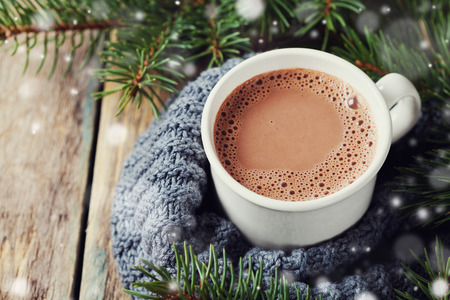 Photo pour Cup of hot cocoa or hot chocolate on knitted background with fir tree and snow effect, traditional beverage for winter time - image libre de droit