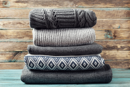 Photo pour Pile of knitted winter clothes on wooden background, sweaters, knitwear, space for text - image libre de droit