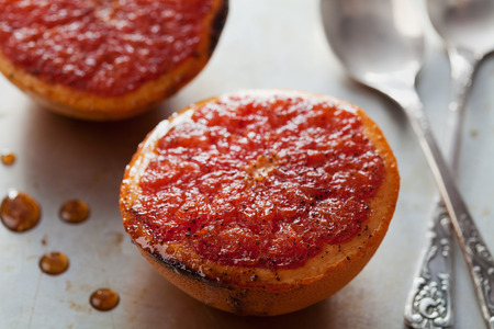 Vintage image of broiled grapefruit with brown sugar and cinnamon on metal surface, healthy dessert is good for breakfast or snacks