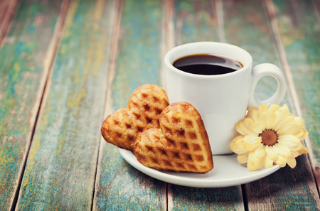 Photo pour Waffle biscuits in shape of heart with cup of coffee and flower on rustic background for Valentines day, vintage toned - image libre de droit