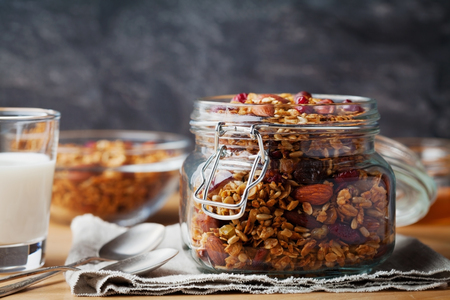 Homemade granola in jar on rustic table, healthy breakfast of oatmeal muesli, nuts, seeds and dried fruit