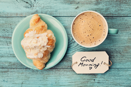 Photo for Coffee mug with croissant and notes good morning on turquoise rustic table from above, cozy and tasty breakfast, vintage toned - Royalty Free Image