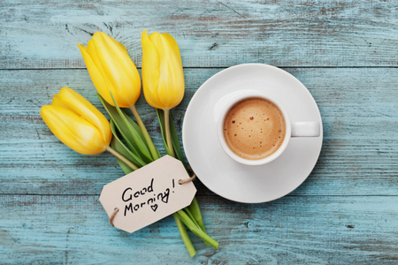 Coffee mug with yellow tulip flowers and notes good morning on blue rustic table from above, breakfast on Mothers day or Womens day