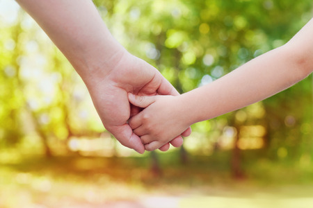 Foto de Fathers hand holding his little child in sunny day outdoor, united family and happy childhood concept, beautiful bokeh background - Imagen libre de derechos