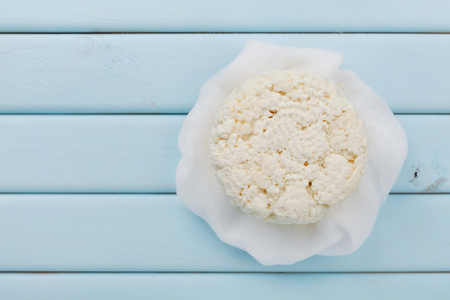 Homemade cottage cheese or curd on light blue table, rustic style, top view