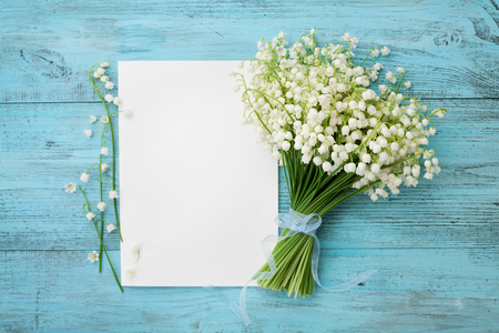 Photo pour Bouquet of flowers lily of the valley and empty paper sheet on turquoise rustic table from above, beautiful vintage card, top view, copy space for text, flat lay - image libre de droit