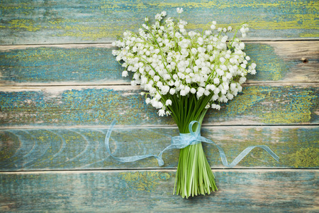 Foto de Beautiful bouquet of flowers lily of the valley on vintage wooden table from above, rustic background - Imagen libre de derechos