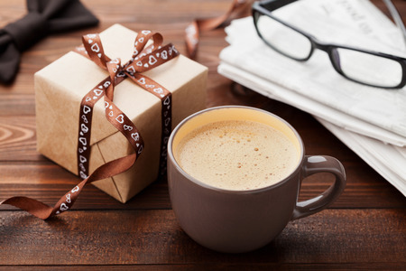Foto de Morning cup of coffee, gift, newspaper, glasses and bowtie on wooden desk for breakfast on Happy Fathers Day - Imagen libre de derechos