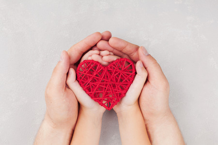 Foto de Adult and child holding red heart in hands top view. Family relationships, health care, pediatric cardiology concept. - Imagen libre de derechos
